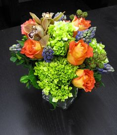 Green Hydrangeas, orange Roses, Orchids, and blue Hyacinth makes an eye-catching fall arrangement of NYC fresh cut flowers.