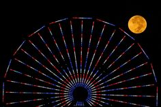 """""""The moon is pictured behind a Ferris wheel on the pier in Santa Monica, California after a total lunar eclipse, also known as a 'blood moon', on October The coppery, reddish color the moon takes is made as it passes into Earth's shadow."""