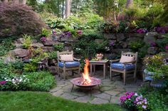 Patio with a fire pit with rock retaining wall with plants - very inviting and feels private.