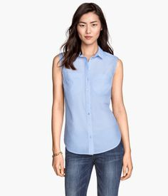 Straight-cut sleeveless shirt in woven cotton fabric. Chest pockets, buttons at front, and a rounded hem. Slightly longer at back.