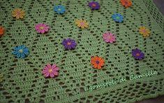 Copertina a uncinetto con rombi e piccoli fiori applicati