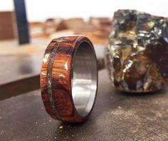 Each or our rings is a handcrafted one of a kind piece, and is made to  order for you and your significant other by a passionate and skilled  artisan. This ring features an ironwood overlay with an amber inlay.  Different wood and stone options available upon request.  Available in: TITANIUM, S