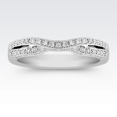 The slight curve in the center of this wedding band serves as the perfect accompaniment to the engagement ring of your choice. Crafted from 14 karat white gold design, this innovative style includes fifty-three hand-selected, pavé-set round diamonds at approximately .25 carat total weight. With a double band appearance, the celebration of an anniversary is also symbolized.