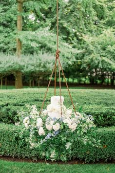 "From the editorial ""A Whimsical Alice in Wonderland Inspired Fête at a Private Lake Forest Estate"". ""From the gorgeous hanging floral cake to the mismatched chinoiserie to the abundance of topiaries to the modern blue tent, this garden party wedding was simply stunning"" 