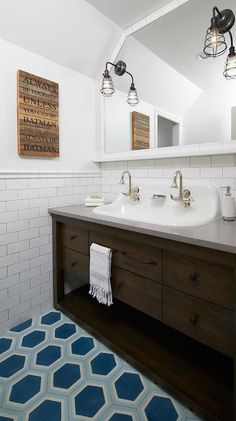 Well appointed kids' bathroom features blue hexagon floor tiles leading to a brown washstand accented with a shelf, oil rubbed bronze pulls, and a gray quartz countertop fitted with a trough sink completed with 2 nickel faucets located in front of white subway tiles beneath a white tiled mirror lit by black industrial sconces.