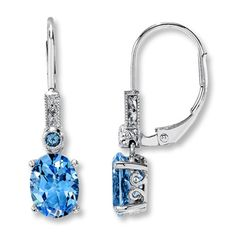 Oval and round blue topaz dangle beneath diamonds in each of these lovely earrings for her. Crafted in 10K white gold with milgrain edging, these fine jewelry earrings are secured with euro-wire backs.  Topaz is  commonly subject to enhancement processes or treatments such heating, irradiation and diffusion, which may not be permanent and may require special care.  Gently clean by rinsing in warm water and drying with a soft cloth, and avoid chemicals, strong light, heat and ultrasonic…