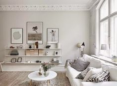 Light coloured wood flooring, modern white shelving, table and rug. Via Coco Lapine Design via Entrance.