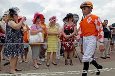 Jockey Garrett Gomez's silks fit right in with the crowd's fashion as he makes his way to the paddock for the fifth race Friday.
