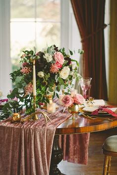 Gorgeous and romantic tablescape. An overflowing centerpiece of flowers and greenery, shimmering table linens draped over the table, and elegant candle sticks with gold accents. So pretty!