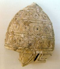 An ivory relief from Phaistos Crete XVI Century BC, represents a conical helmet with small cheek and neck guards. Also in this case the reinforcement disks were probably made of ivory or metal