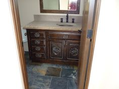 Artisan carved vanity by Carved Custom Cabinets.