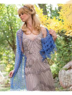 The crochet shawl is worked end to end as a simple mesh rectangle, ending with lace crosses.