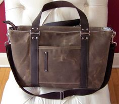 Durable diaper bag for your own use or as a beautiful gift. Made out of heavy duty waxed canvas with oil tanned leather accents-even HE wont mind carrying this around! Features 2 exterior pockets and 5 interior pockets: 2 slip pockets on one side and 3 bellows pockets on the other. Fully lined with cotton twill. Shoulder strap is removable and adjustable for multiple carrying options. Zip top keeps interior items secure. Current exterior colors available include: 19 ounce waxed canvas in…