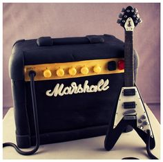 """MARSHALL AMP & FLYING V GUITAR BIRTHDAY CAKE6x6x4"""" 4 layer vanilla sponge & buttercream filled cake. Covered in black fondant/sugar paste and gum paste detailing. Complete with a hand made detailed gum paste Gibson Flying V guitar."""