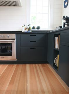 Gray kitchen cabinets and wood floor in Goode Kitchen, Amagansett
