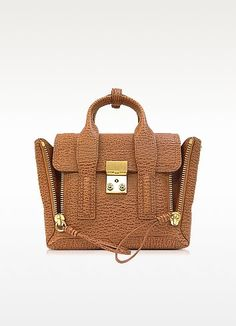 €790.00 | Pashli Caramel and Cognac Leather Mini Satchel crafted in textured leather, is a small but powerful pouch with a cool vibe. Featuring detachable shoulder strap, double top handles, flap top with push lock closure, exterior zipper gussets to create a fan silhouette and internal zip pocket. Signature dust bag included.