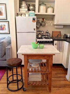 Una mesa auxiliar hace de isla de cocina, mesa y escritorio