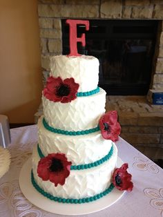 Textured white buttercream cake with teal border and red poppy flowers