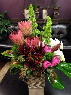 Tropical floral arrangement with Protea, Orchids, peonies, Belles of Ireland, and Ti leaves. Tropical Centerpieces, Tropical Floral Arrangements, Large Flower Arrangements, Large Flowers, Silk Flowers, Altar Flowers, Church Flowers, Funeral Flowers, Flowers Garden