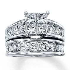 A quartet of sparkling princess-cut diamonds is showcased in this breathtaking diamond engagement ring for her.  Brilliant round diamonds are channel-set along either side of the 14K white gold band. The matching wedding band features additional round channel-set diamonds for added brilliance. This sensational diamond bridal set has a total diamond weight of 4 carats. Diamond Total Carat Weight may range from 3.95 - 4.11 carats.