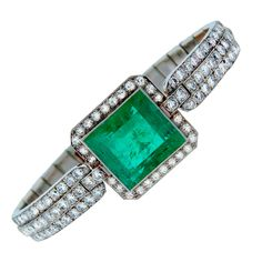 Breathtaking Art Deco bracelet created in the 1920's - 1930's. Features a gorgeous about 15-ct square emerald tastefully framed with round diamonds set in platinum.