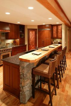 A dark wood kitchen with a stone and wood island. What do you think of the colored glass design?