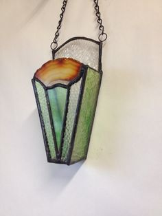 Terrarium wall sconce with unique agate accent, textured clear and green streaked glass, translucent green triangle. 7 1/2 x 3 1/2 x 2. Additional 7 chain for hanging. Air plants, pebbles not included.