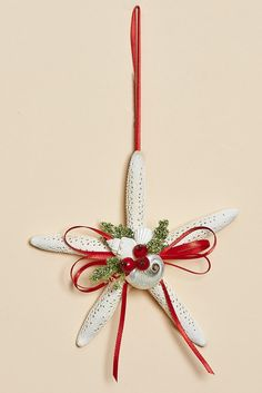 Delightful white finger starfish ornaments created with white shells, and red ribbon.