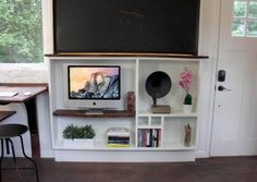 Handcrafted Movement Tiny House 0018. desk/eating space next to a smart shallow flat screen and doodad shelf unit.