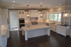 Beautiful kitchen features a white French range hood situated over a red brick herringbone cooktop backsplash and an integrated gas cooktop next to double ovens.
