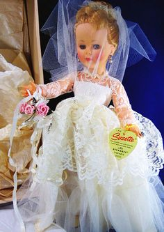 """.99 cent___Vtg Beautiful Bride in Gown Doll Retro 1970 14"""" Tall Suzette Effanbee Durable As ___ Hi there...... stunning mid century bride in her white gown, veil, engagement ring, by Effanbee Durable Doll. Say hello to the blonde Suzette with high color cheeks, rooted blonde hair and in her original box.  Measuring 14"""" tall, she has her earrings, and wrist tag, shoes, nylons and garter belt.   Wonder doll collectible or for the modern wedding vintage display piece. She comes with a display stand for the home interior diy accent piece.  The box shows some wear, and there is a slight tear in the box."""
