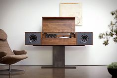 The Symbol Record Console is a bench-made modern record player that pays homage to the all-in-one console hi-fis of the '50s. Features include solid American Walnut construction, a metal base, two 6.5-inch full-range speakers, a second, hidden amplifier and subwoofer, built-in Wi-Fi for streaming music from an iPhone, iPad, iPod, or computer, and a hand-built tube amplifier and turntable, which are set into patinated steel plates