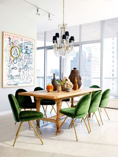 Unique dining room with light hardwood floors, a wall of windows, wooden dining table, oversized art and emerald green dining chairs | Nate Berkus