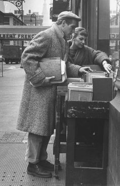Actor Paul Newman looking through books for sale with his wife, Joanne Woodward. Photograph by Gordon Parks. New York City, March 1959.
