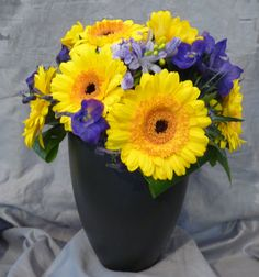Black container of vibrant yellow and purple flowers. Surrey, Corporate Events, Purple Flowers, Floral Arrangements, Container, Vibrant, Seasons, Yellow, Black