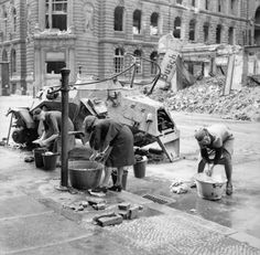 German women doing their washing at a water hydrant in a Berlin street, near the wreck of a German light armoured car, 3 July 1945. Germany Under Allied  Occupation (BU 8609). Imperial War Museums.