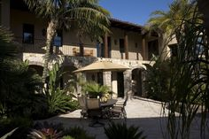 Front Exterior:  Mediterranean, Tuscan, European architecture, stucco, smooth stucco, balcony, wrought iron, decorative iron, tile roof, stucco chimney, detailed fascia, wood windows, wood casement windows, wood French doors, French door, arch widow, arch wood casement windows, outdoor lighting, custom wood garage door, pillars, stone exterior walls, stucco walls, wood walls, upstairs balcony, balcony wrought iron railing, title roof, landscaping.