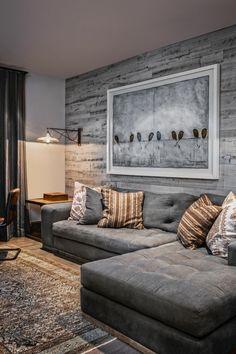 Idéias de design de parede na sala de estar com sofá de canto cinza e tapete elegante.
