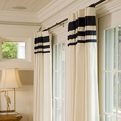 Wide bands of fabric at the headings of these draperies turn ready-made into a bolder statement. Get this look for your home by purchasing inexpensive solid curtain panels and adding horizontal bands of fabric or ribbon in decreasing widths. Try strips in 1-, 2-, and 4- inch widths, evenly spaced.