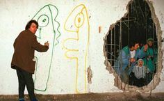 Thierry Noir paints the other side of the Berlin wall, reached through a hole.
