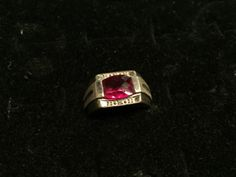MENS STERLING SILVER RING WITH RED STONE AND DIAMOND CHIPS. SHOWS GENTLE WEAR. SIZE 10.