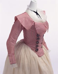 "This women's jacket features a distinctive large turned-down collar with scalloped edges. Metallic large buttons placed in two rows provide accent.The British lifestyle of enjoying rural life and hunting in natural surroundings also became popular in France, and the clothes became more simplified in and after the 1770s. ""Redingotes,"" or riding coat, which had been popular among men for horse riding or traveling, influenced women's clothes, resulting in sophisticated jackets like this."