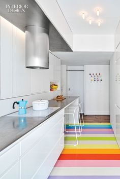 SABO Invigorates a Fashion Forecaster's Paris Apartment with a Cheerful Array of Colors | The kitchen of a fashion forecaster's apartment features a cheerful array of 6-inch-wide rubber flooring strips—25 in all. #interiordesign #design #interiordesignmagazine #projects #cityapartments