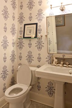 Navy and white traditional bathroom with Thibaut's St. Barth's wallpaper, traditional pedestal sink, Restoration Hardware fixtures, and classic Carrara Marble hexagon tiled floor || by Michael Robert Construction, via Houzz