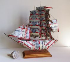Interesting piece of art work here...a clipper ship made of genuine Budweiser cans! It sits on a wooden base.    measures: 13.5 tall  14 wide  3.5 deep    In decent condition. The front part of the ship has some of the paint worn off of the aluminum. You will get some light dust with this. I think there must have been 3 flags on the top, only one remains. The edges are kind of sharp so if you get this...be careful!    Please convo for a shipping quote outside of the USA. Thanks…