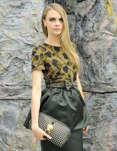 Cara Delevingne in gorgeous outfit: Abstract floral patterned top in beige, black and yellow, beautiful draped skirt with a bow, in subdued olive colour, super cool clutch from the Burberry Autumn/Winter 2012 collection featuring whimsical dog labrador buckle.