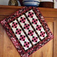 SALE - Just in time for February, this wonderful pink and chocolate brown nine patch is set in rows on point. Each row is sashed with chocolate