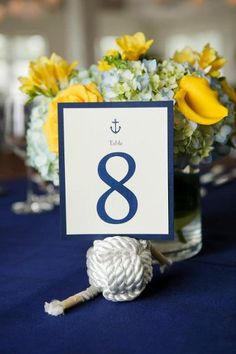 Nautical wedding centerpieces of blue hydrangea, yellow callas, roses and freesia