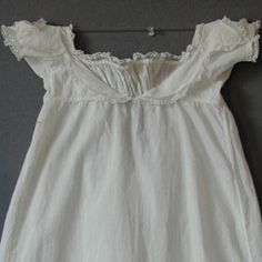 Toddler's dress  c 1805  of fine white cotton, the high bodice with low curved collar with double points over the short puffed sleeves, all edged in bobbin lace, the front with a gathered infill, lace trimmed, drawstring at back opening, the hem with six pleats, shoulder to hem 22 1/2 in or 57 cm; width 10 1/2 in or 27 cm.  Meg Andrews