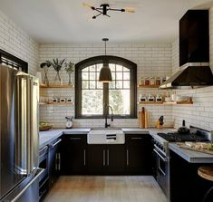 Ivory ceramic backsplash tiles frame a kitchen wall displaying wraparound floating wood shelves flanking a center window over a farmhouse sink with an oil rubbed bronze gooseneck faucet.